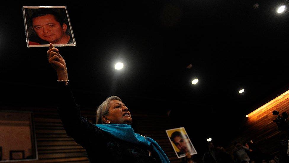 Una mujer levanta una foto de un hombre desaparecido en Coahuila