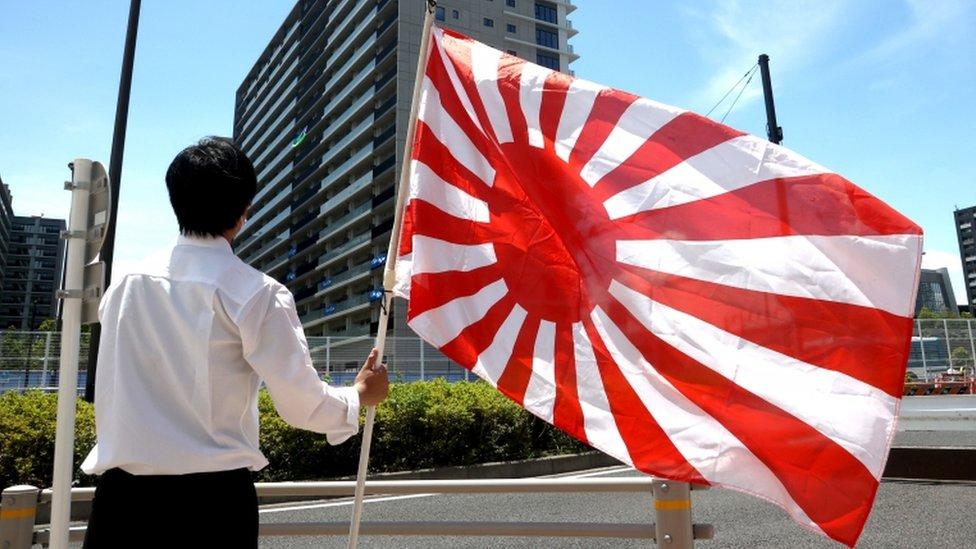 Un miembro del grupo ultraderechista japonés sostiene la bandera del Sol Naciente frente al edificio donde se aloja el equipo olímpico de Corea del Sur en la Villa de Atletas Olímpicos de Tokio, Japón, el 16 de julio de 2021.
