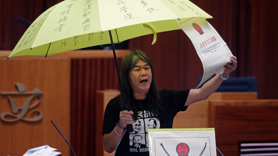 """Newly elected pro-democracy lawmaker Leung Kwok-hung, known as """"Long Hair,"""" holds a yellow umbrella and a oversized mock copy of controversial, proposed anti-subversion legislation as she takes the oath in the new legislature Council in Hong Kong, Wednesday, Oct. 12, 2016"""
