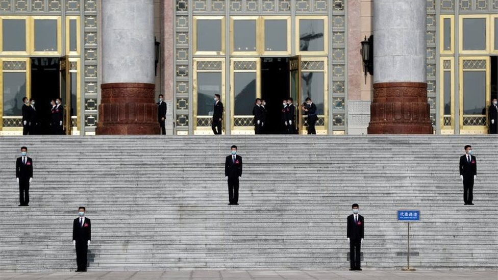 "Security personnel wearing face masks following the coronavirus disease (COVID-19) outbreak stand guard outside the Great Hall of the People before the opening session of the National People""s Congress (NPC) in Beijing, China May 22, 2020."