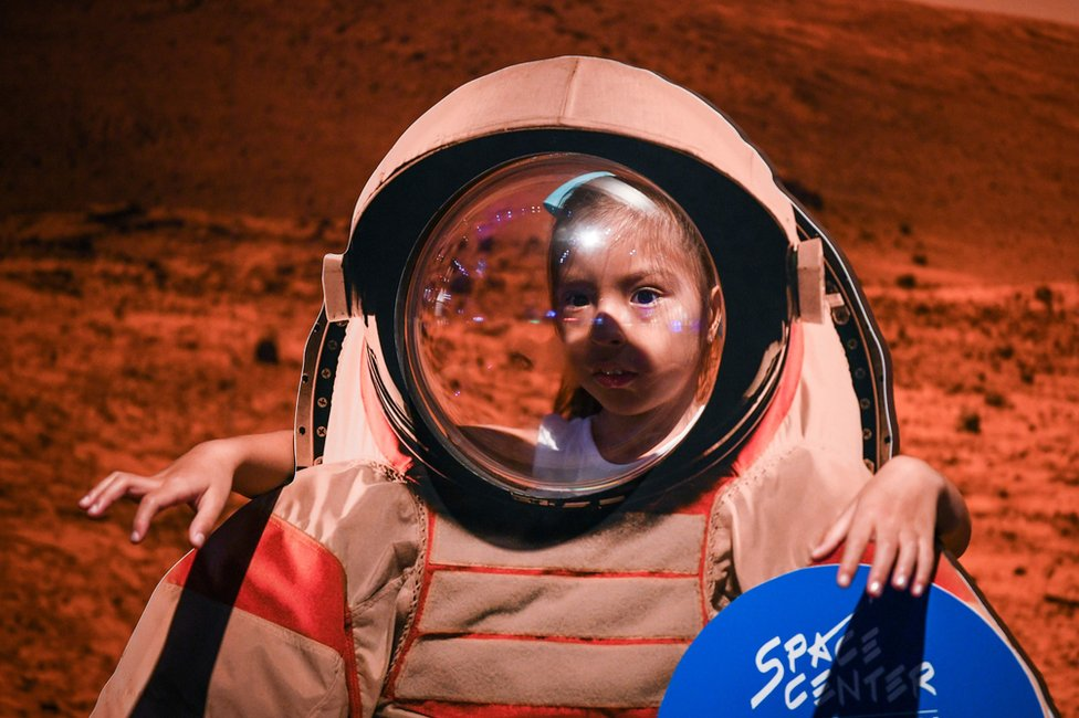 A young girl looks at an exhibit during the Apollo 11, 50th Live celebration at Space Center Houston