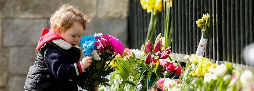 A child holds a bouquet of flowers outside Windsor Castle