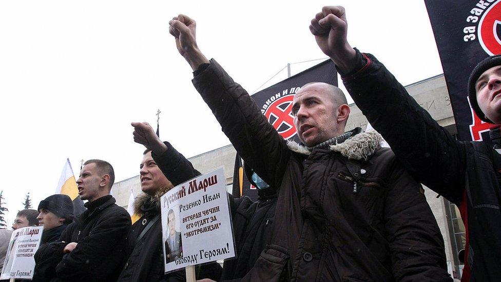 Extremistas nacionalistas rusos sostienen carteles contra los inmigrantes durante una protesta.