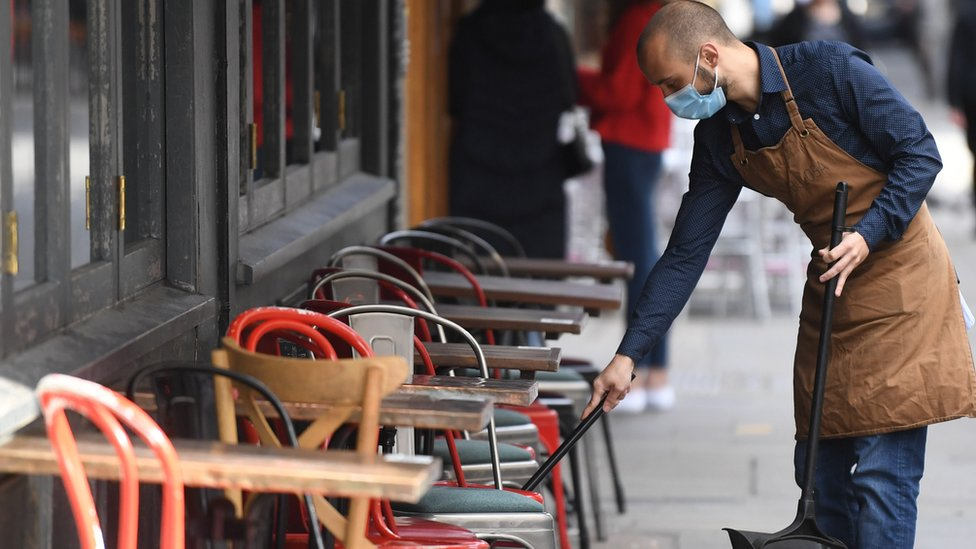 Man cleans outside seating of London pub