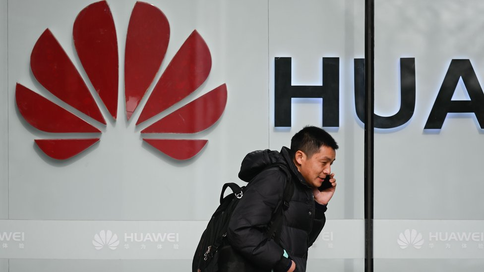 A pedestrian talks on his phone while he walking past a Huawei store in Beijing on January 30, 2019