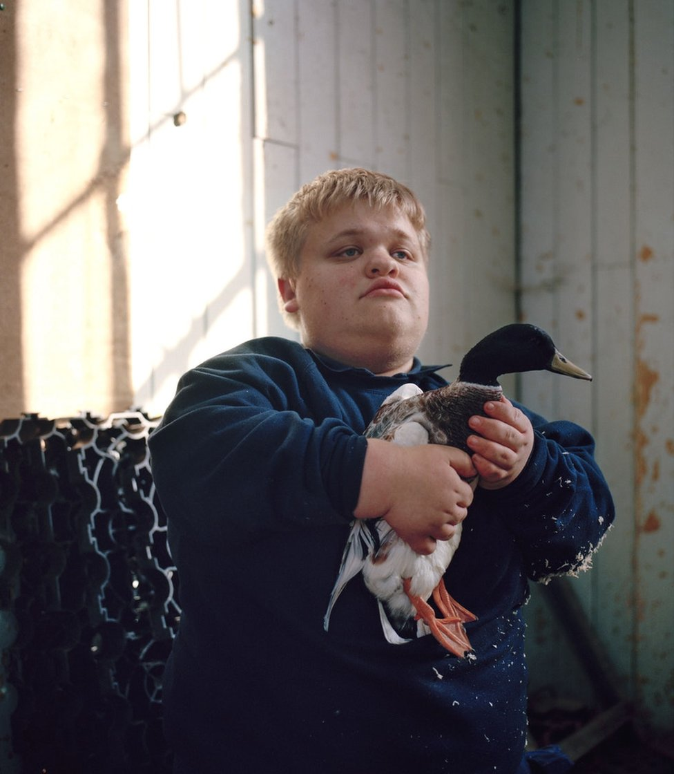 A boy holding a duck