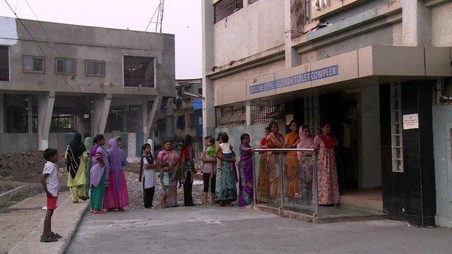 Women queue to use the public toilet in Mumbai