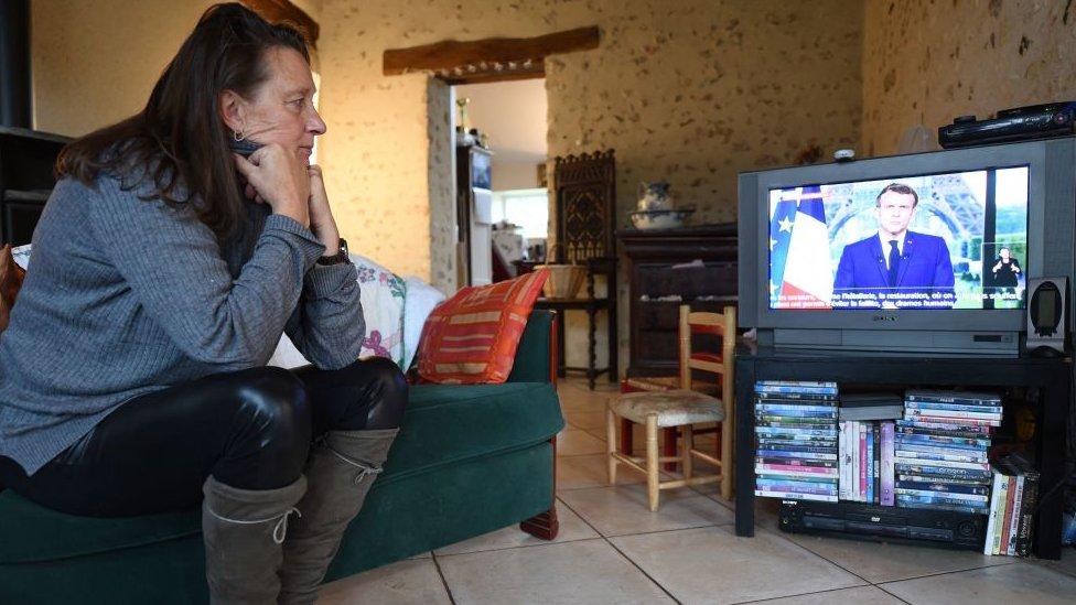 Bir hemşire Fransa Cumhurbaşkanı Macron'un açıklamalarını dinliyor