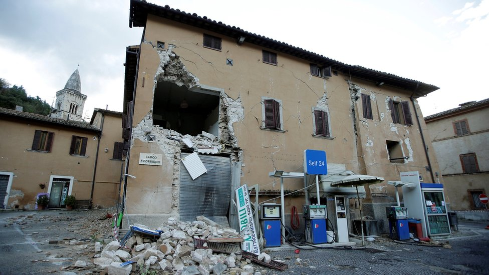 A collapsed building is seen next to a petrol station after an earthquake in Visso, in central Italy