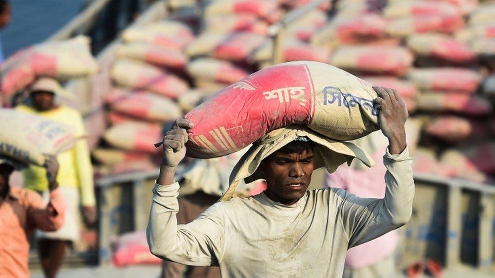 Trabajador descarga un saco de cemento de un buque cerca de Daca, febrero 2020.