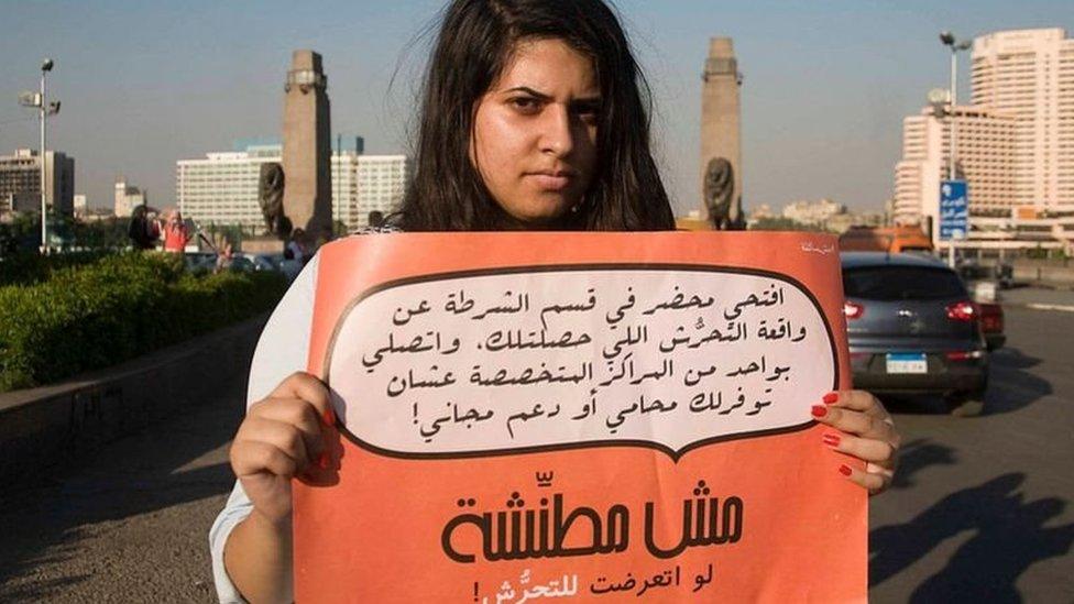 فتاة تحمل لافتة تطالب الضحايا بعدم الخوف