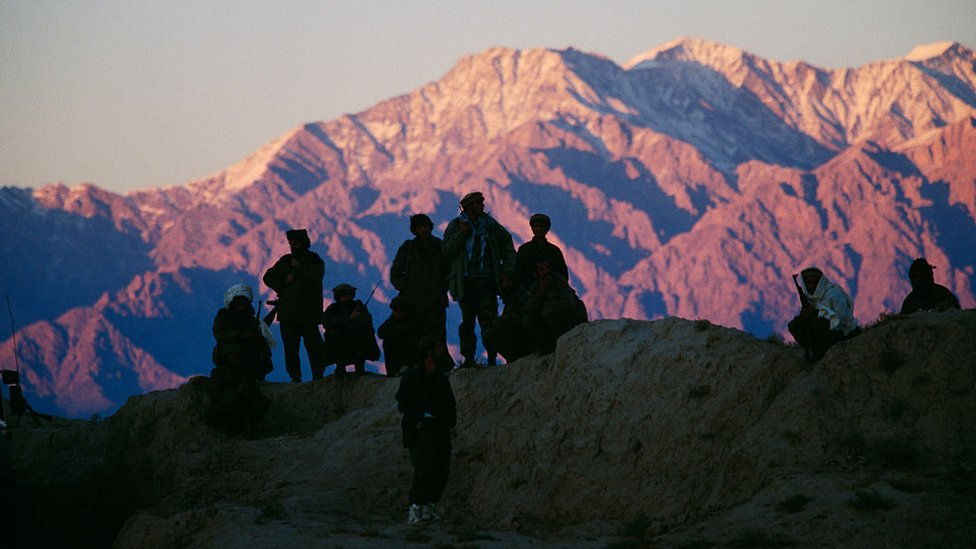 A group of soldiers are silhouetted against a mountain backdrop