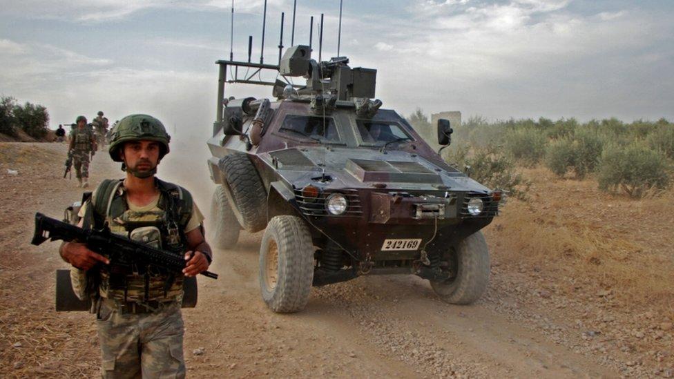 جندي تركي يسير بالقرب من مركبة مدرعة على مشارف منبج شمال سوريا