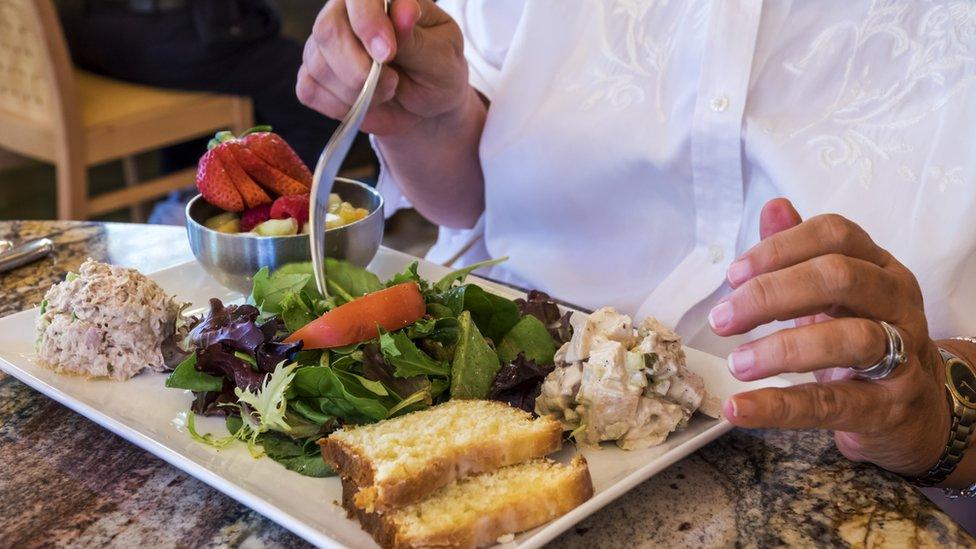 Mujer ante un plato de comida