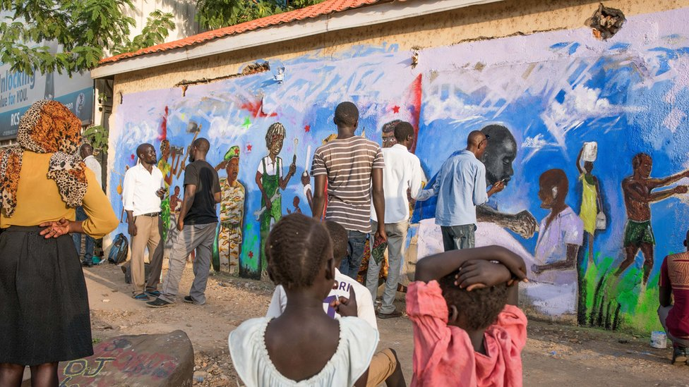 People gather round a mural depicting various different figures in society, eg doctors, soldiers and mechanics.