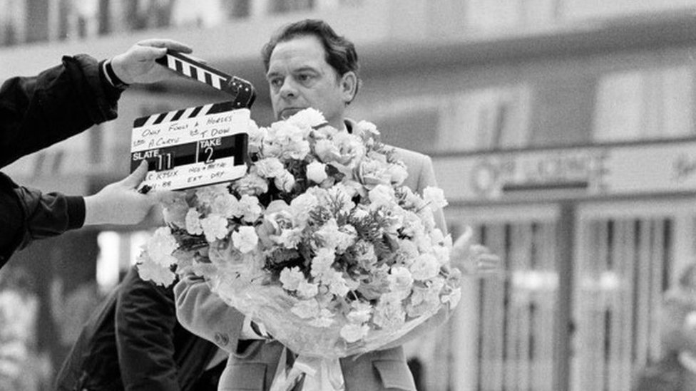 Black and white photo of David Jason carrying a huge bunch of roses