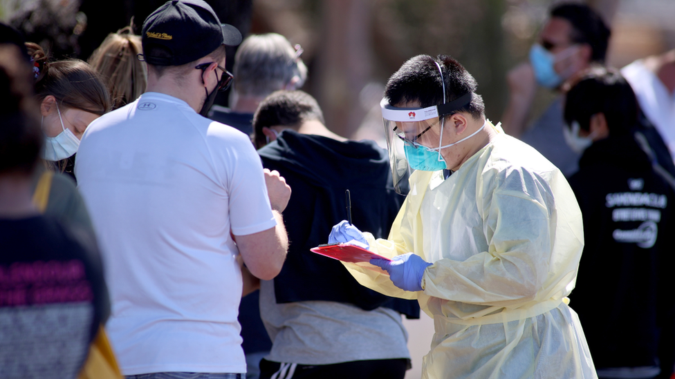 A healthcare worker wearing full protective equipment records details of people queuing to get tested