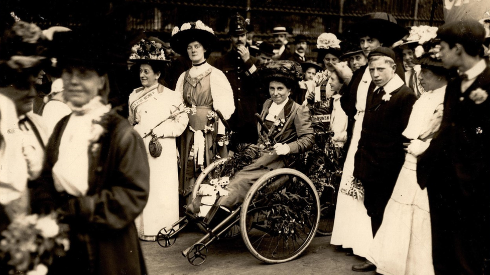 A black and white photo of Rosa at a rally surrounded by her fellow suffragettes. She wears a hat and a long dress.