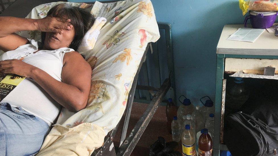 Una mujer en una cama de hospital con botellas de agua en el piso