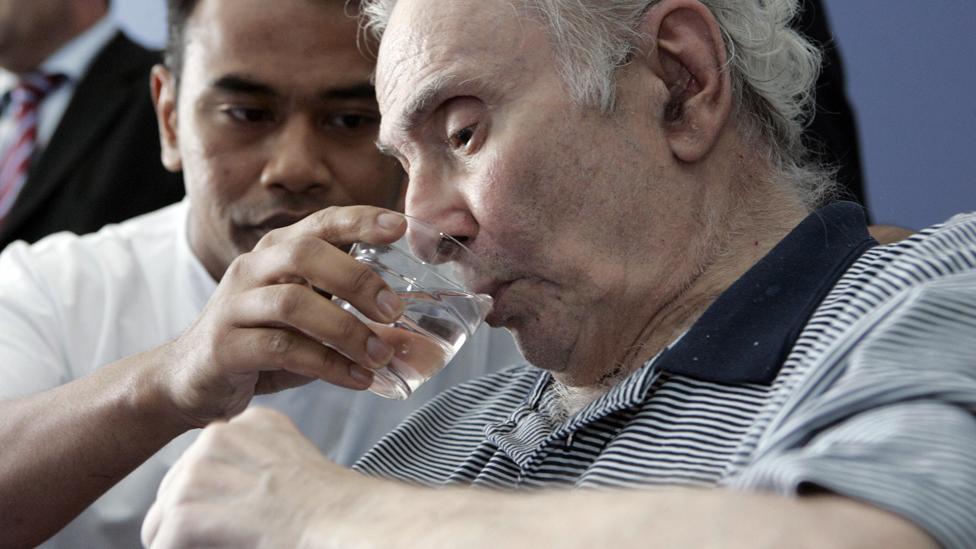 Una ayudante da agua para beber a un hombre de edad avanzada