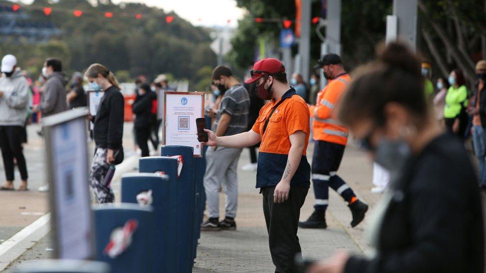 Filas de pessoas usando um 'QR code' para fazer check-in em um estádio de Sydney para a vacinação