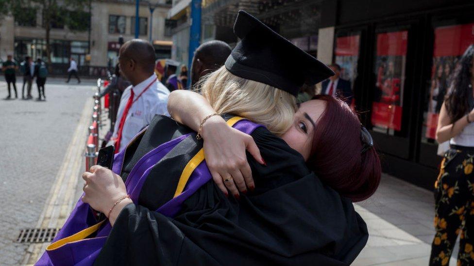 Dos graduadas se abrazan.