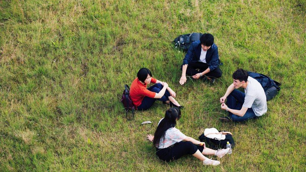 Cuatro jóvenes sentados sobre el césped conversando