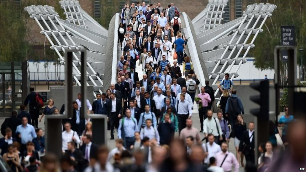 Commuters cross the river Thames on the Millennium footbridge as a tube strike hits the morning rush hour in the city of London