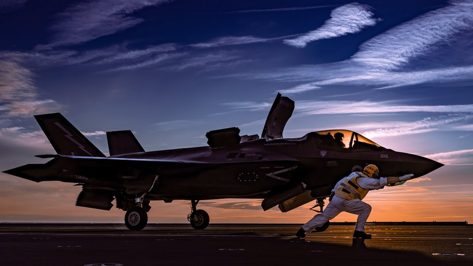 A Lightning jet and pilot silhouetted against a sunset