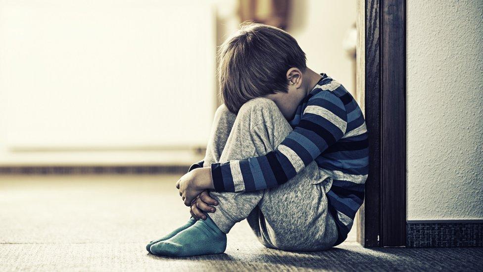 Dečak sedi na podu