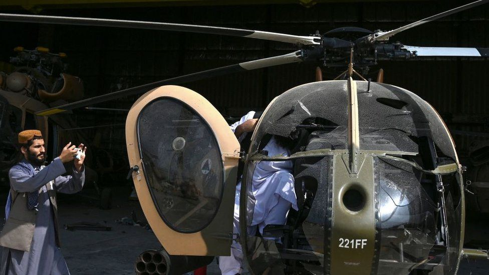 مقاتل من طالبان يلتقط صورة لزميله داخل طائرة مروحية من طراز إم دي-530