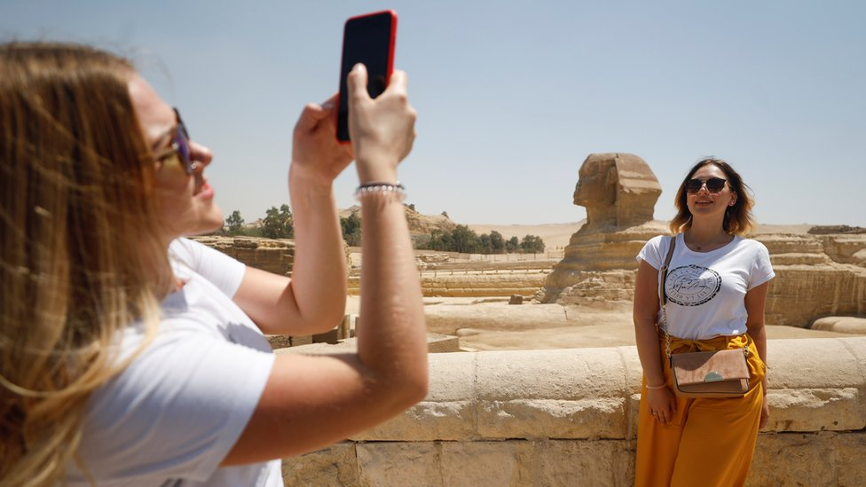 A woman poses for a photo near the Sphinx in Giza, Egypt (1 July 2020)