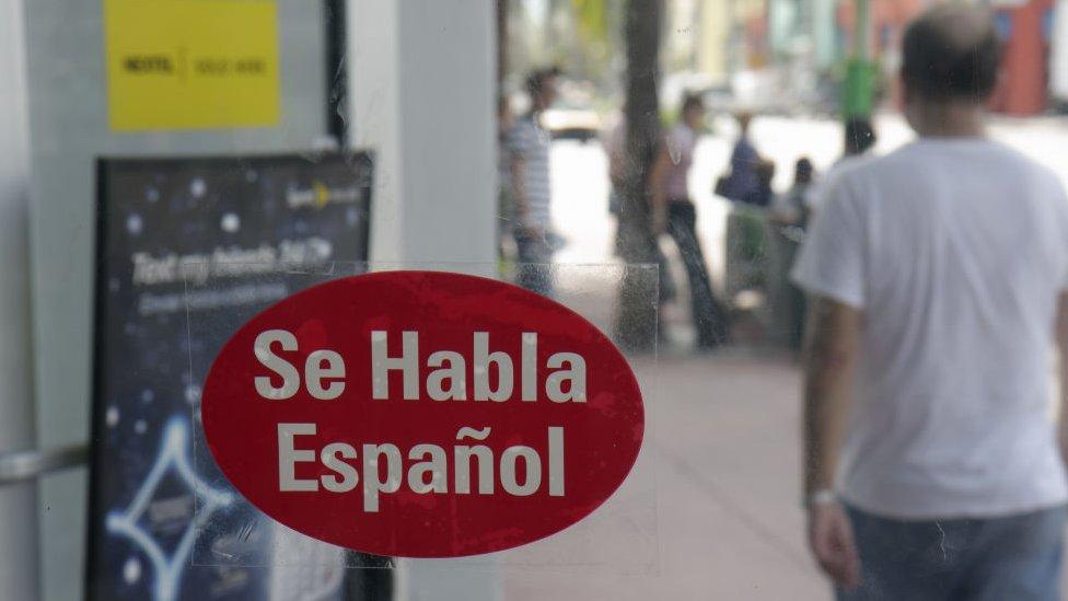"""Una calcomanía pegada en una vitrina dice """"Se Habla Español""""."""