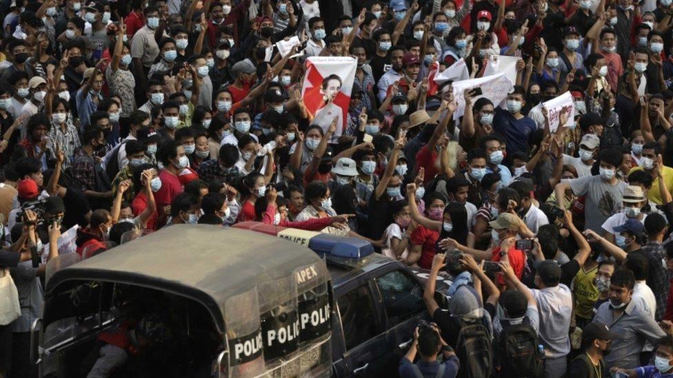 سيارة للشرطة تمر وسط المتظاهرين