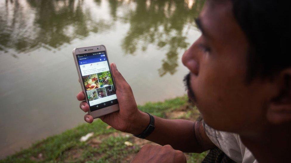 Pripadnik Rohindža sa Fejsbuk aplikacijom na telefonu