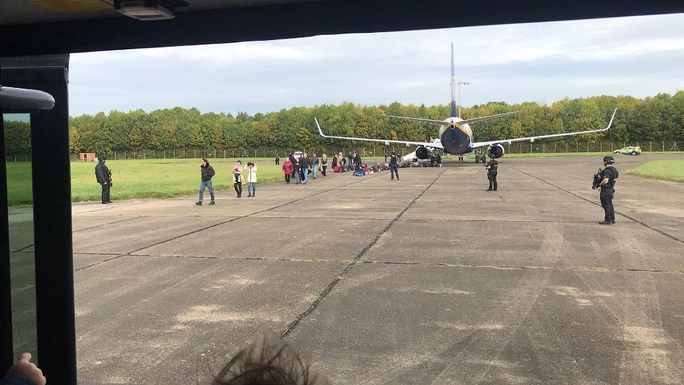 Passengers leave the plane that was escorted to Stansted