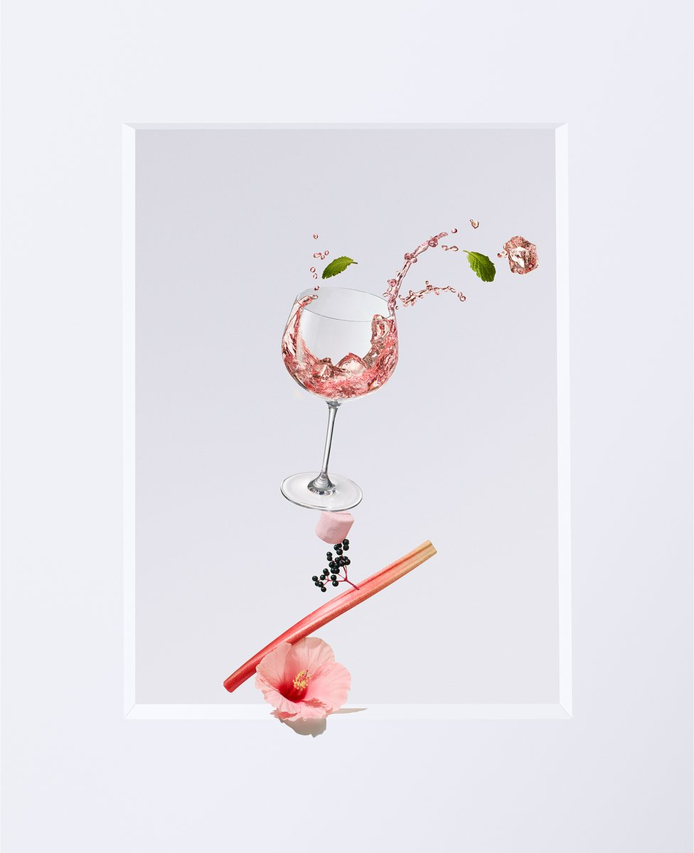 A shot of pink gin in a glass with a flower, rhubarb, berries and a marshmallow underneath
