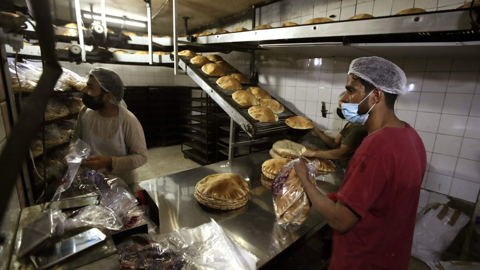 Bakers package workers package freshly-produced bread coming off a production line at an automated bakery in Lebanon