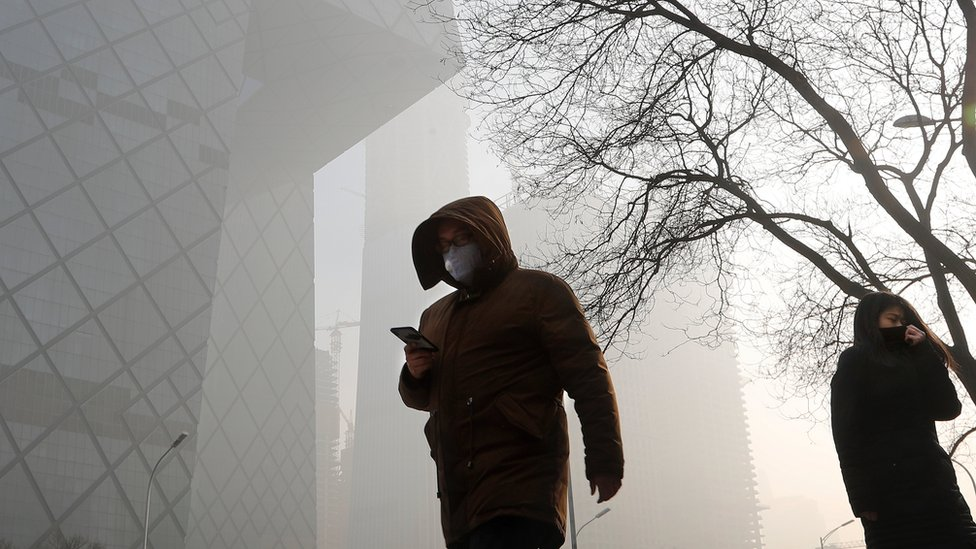 """People wearing protection masks walk near the iconic headquarters of China""""s state broadcaster Central China Television (CCTV) at the Central Business District in Beijing as the capital of China is blanked by heavy smog on 3 January"""
