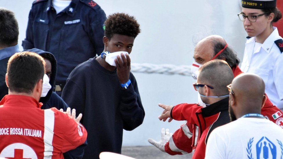A migrant holds breathing mask to his face