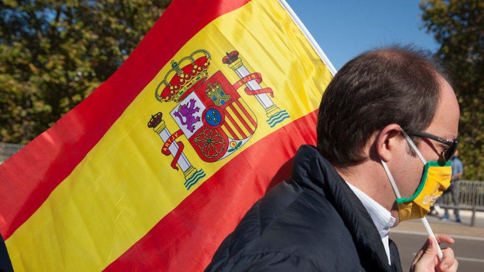 İspanya bayrağı ve maskeli bir kişi