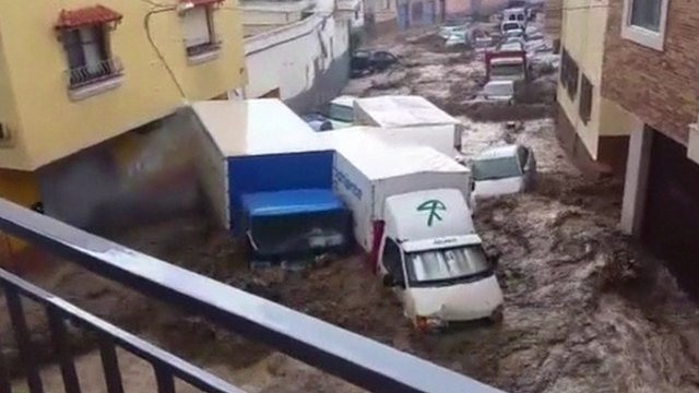 Vehicles washed down a street in the town of Adra