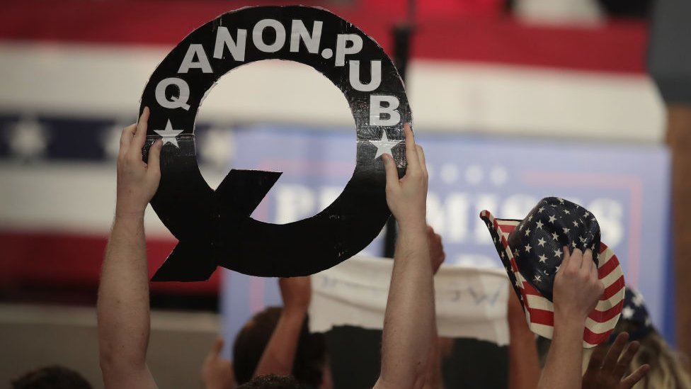 QAnon supporter holds up poster at Trump rally