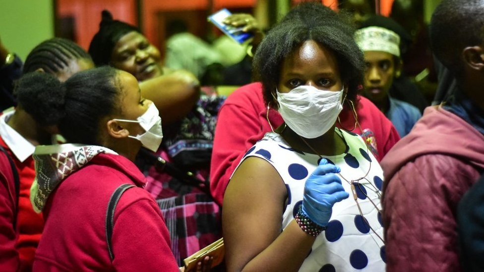Travellers wearing face masks as protective measure wait to get their temperature checked at the border post with Kenya in Namanga