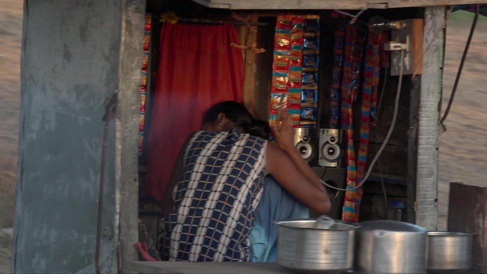 فتاة من Bacchara تخبأ وجهها في نافذة إحدى المحلات