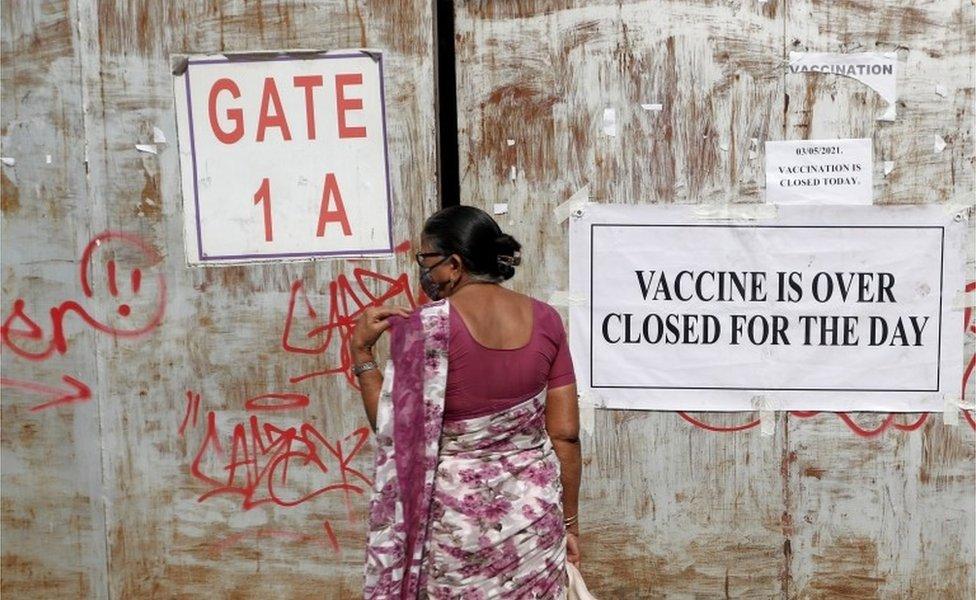 امرأة جاءت لتلقي جرعة من لقاح فيروس كورونا، تقف أمام بوابة مغلقة لمركز التطعيم الذي تم إغلاقه بسبب عدم توفر لقاح، في مومباي ، الهند ، 3 مايو 2021.