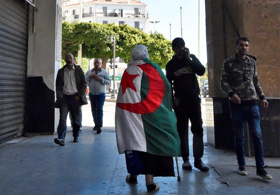 An elderly Algerian woman wrapped in a national flag walks through a colonnade in Algiers.