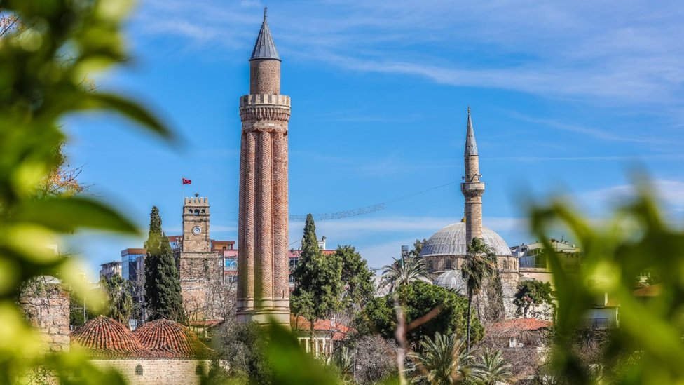 : A view of the Yivli Minaret Mosque and Kaleici clock tower located in the old town of Kaleici, one of the tourist attractions in Antalya, Turkey on March 2, 2018.