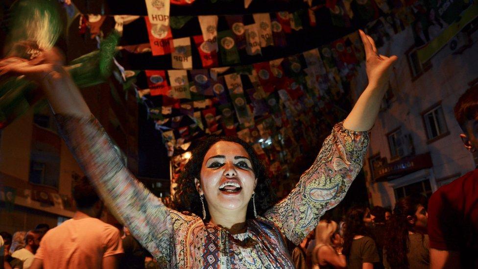Žena pleše ispod plakata kurdske partije u gradu Dijarbakiru