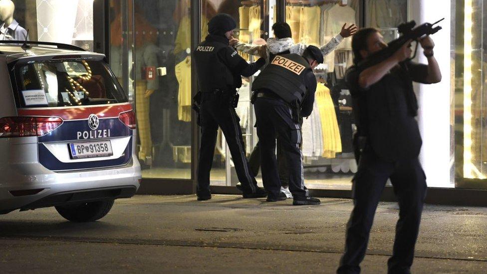 أفراد بالشرطة يفتشون شخصا أثناء قيامهم بدورية في أحد الشوارع